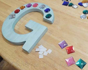 wooden letter in the process of being decorated with decorative plastic jewels