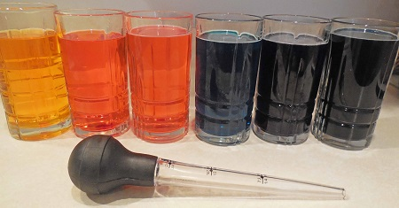six glasses of colored water ready for sugar