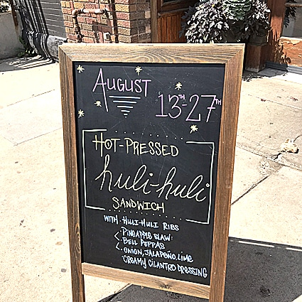 herbivorous-butcher sidewalk sign announcing specials