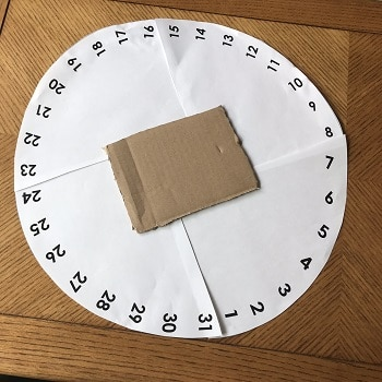 glue cardboard square or circle down over the middle of the numbers circle